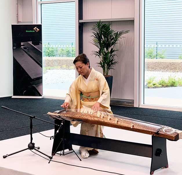 Кейко Китамура играет на японском инструменте кото на открытии центра Sodick